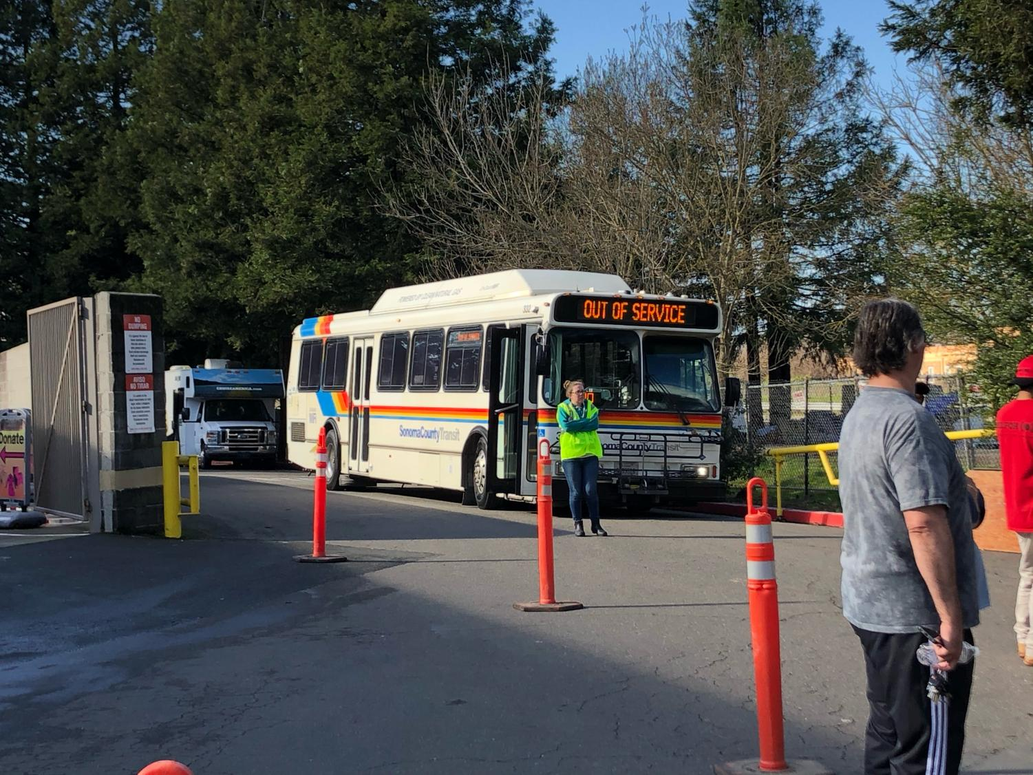 A county bus sits idle waiting to ferry homeless residents, who acquiesce to the county's requests, to their new outdoor camp at Los Guilicos.