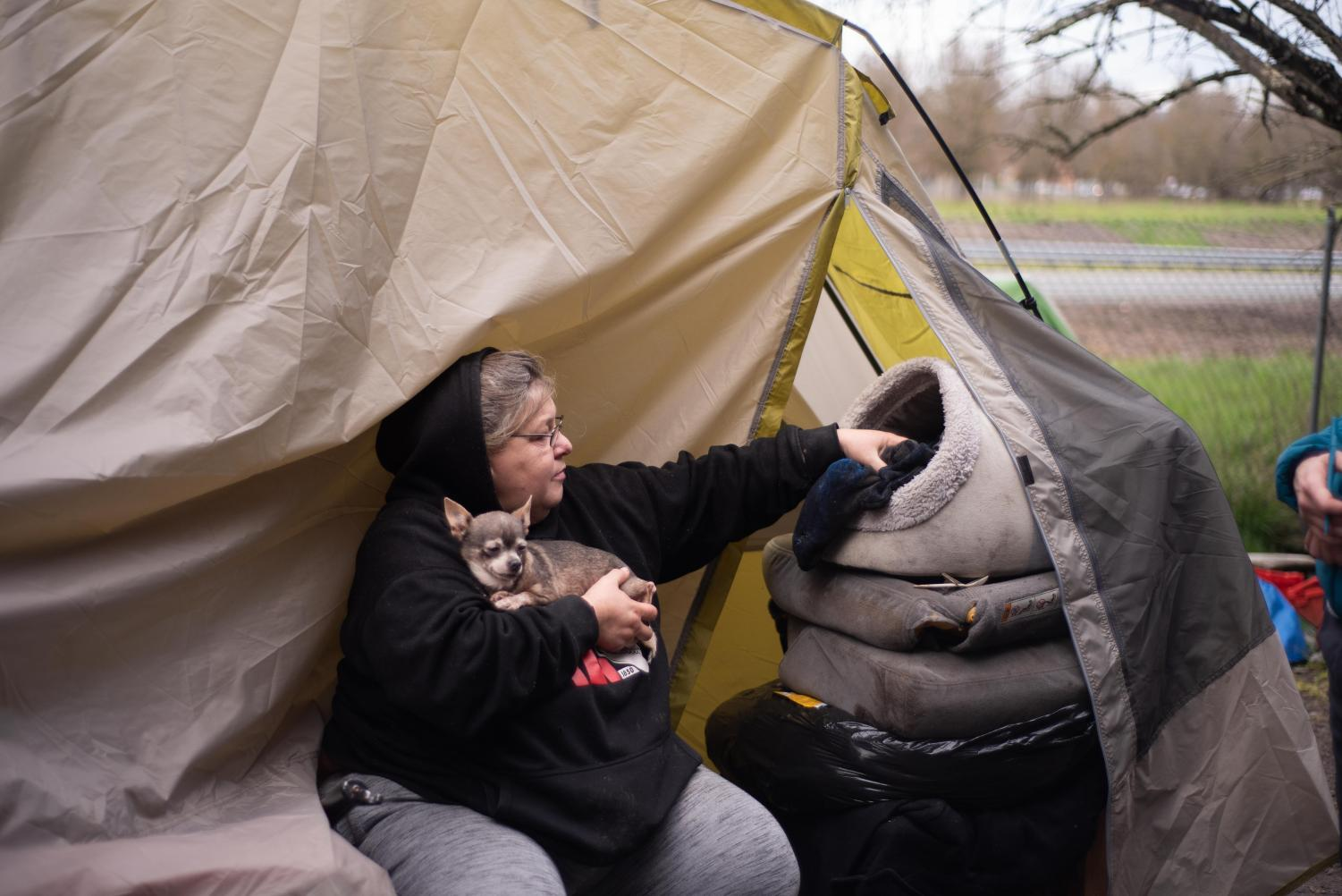 Tina, 50, sits with her chihuahua in her camp on the Joe Rodota Trail.