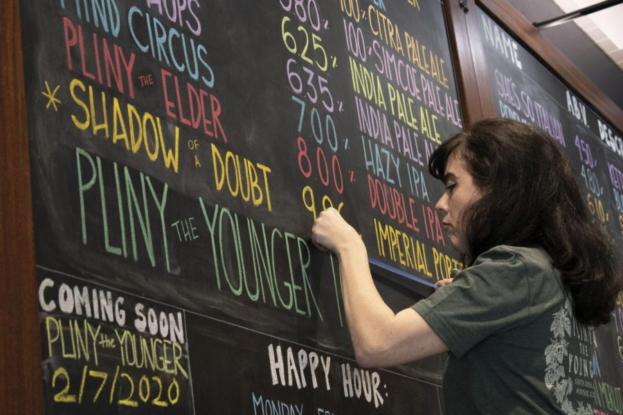Anathea Meade, sign artist for the RRBC, puts finishing touches on the menu board.