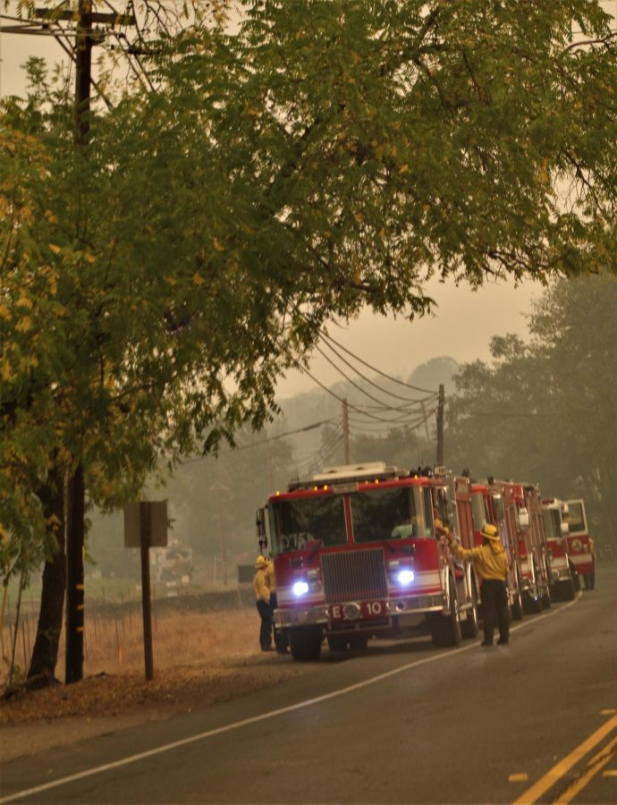 Firefighters shake hands in front of an engine parked on Highway 29.