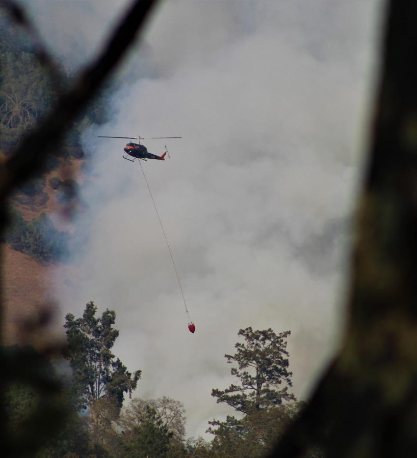 A helicopter carries water to douse the Glass Fire.