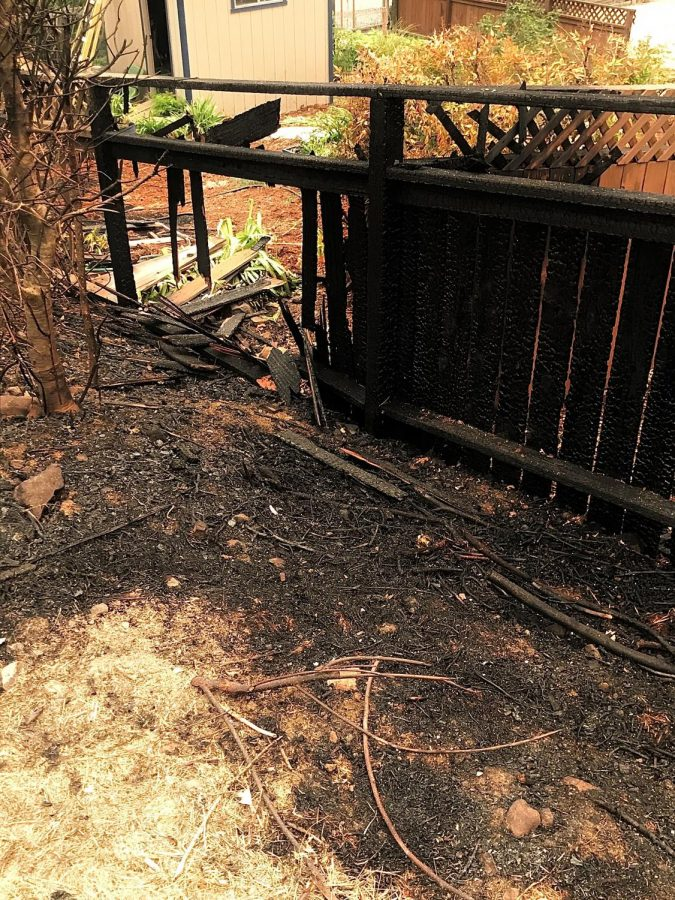 A burned fence sits outside a home on Los Alamos Road that survived.