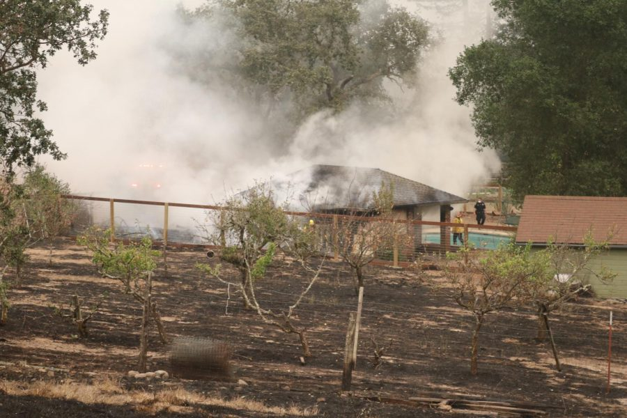 Firefighters extinguish flames on a pool house on Los Alamos Road.