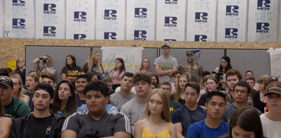 High schoolers sit in a makeshift auditorium after their high school