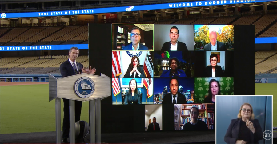 Governor Gavin Newsom stands at a podium in Dodger Stadium in Los Angeles. A screen behind him shows multiple public officials and an ASL interpreter is shown on the bottom right.