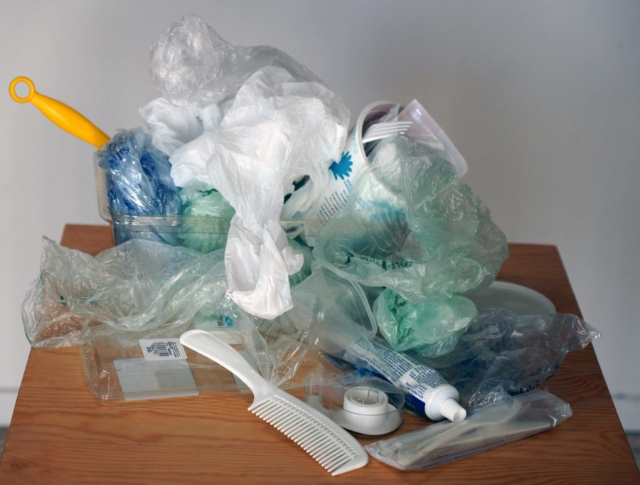 A pile of various pieces of unrecyclable plastic including shopping bags, water bottles and a comb.