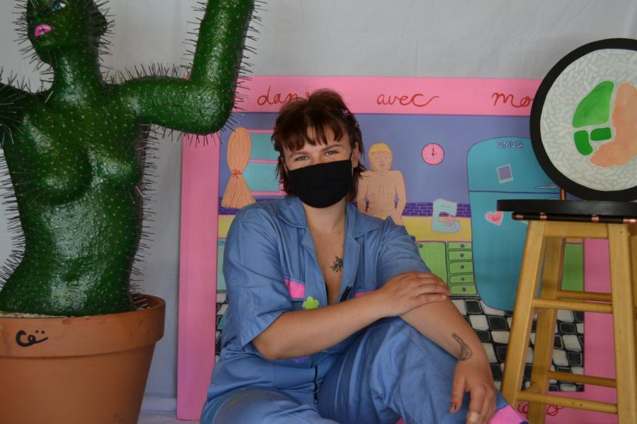 Sydney Gittins, a girl with reddish brown hair and bangs wearing a painted blue jumpsuit, sits in between a few of her art pieces (a cactus woman statue on the left, behind her is a drawn art piece set in a kitchen and on the right is a painted stool).
