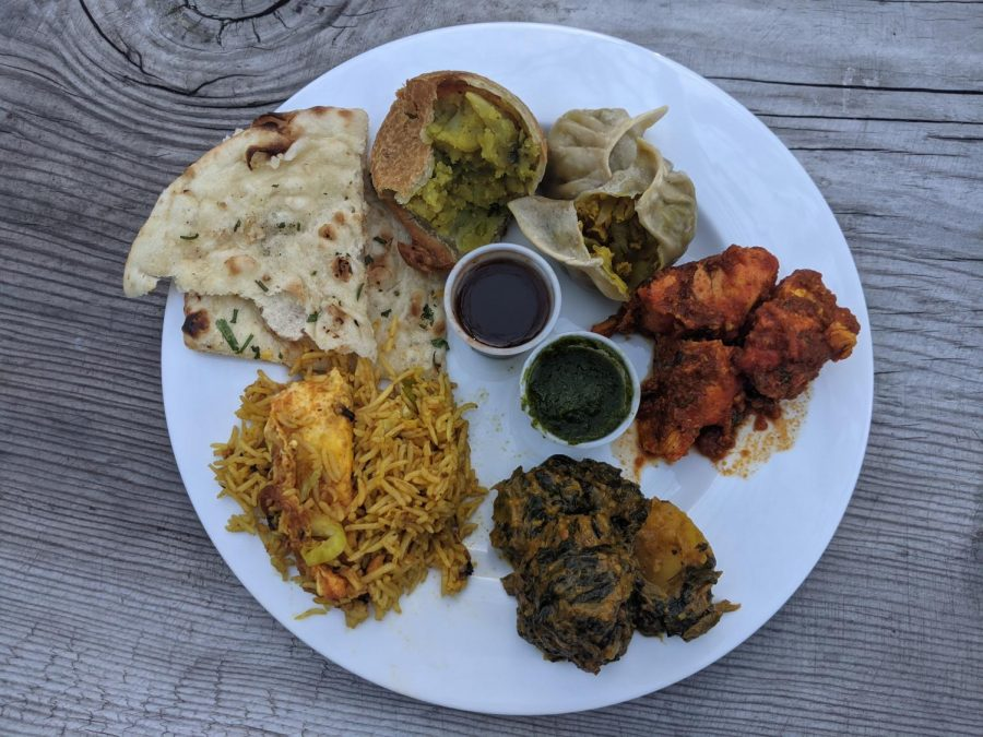 A plate filled with entree options from Cumin Restaurant including naan, chicken choila and aloo saag.