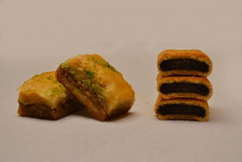 Two pieces of baklava on the left and three stacked pieces of fig newton on the right.