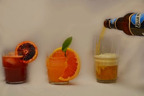Three drinks in a row on a table. The left-most drink is a blood orange kahlua cocktail, the middle is a greyhound cocktail and the last is a beer which is currently being poured into the glass from off screen.