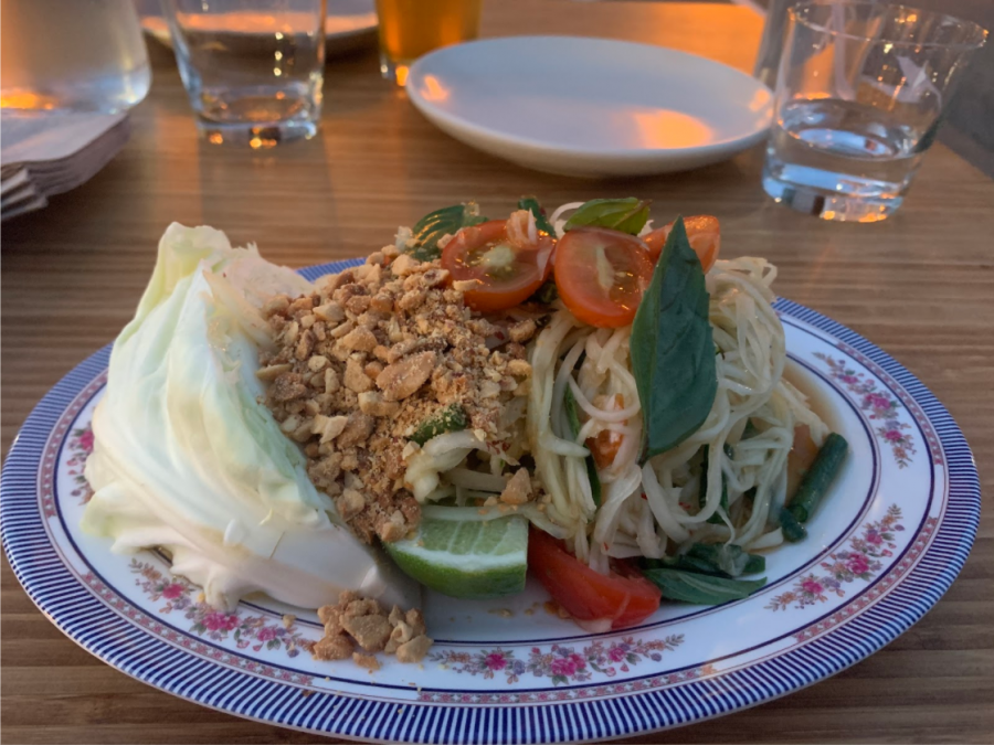 A+plate+of+green+papaya+salad+topped+with+peanuts+and+cherry+tomatoes.