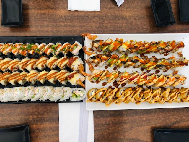 A picture of a black and white platter with servings of sushi from Paradise Sushi & Grill.
