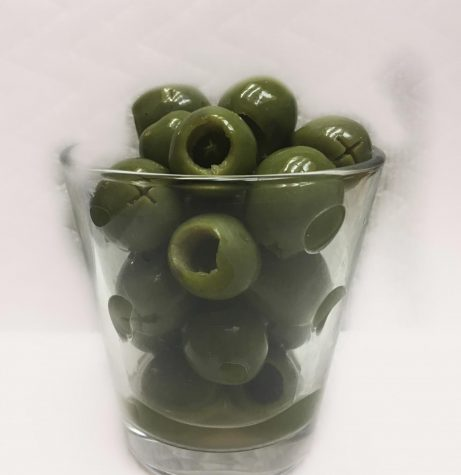 A photo of a shot glass filled with green olives.