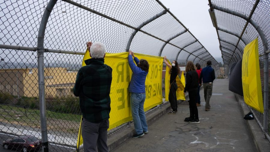 Climate activists hang banners on Highway 101 overpasses to call attention to the climate crisis.