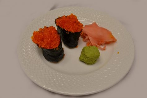 A photo of two pieces of tobiko (fish egg) nigiri with fresh ginger and wasabi.