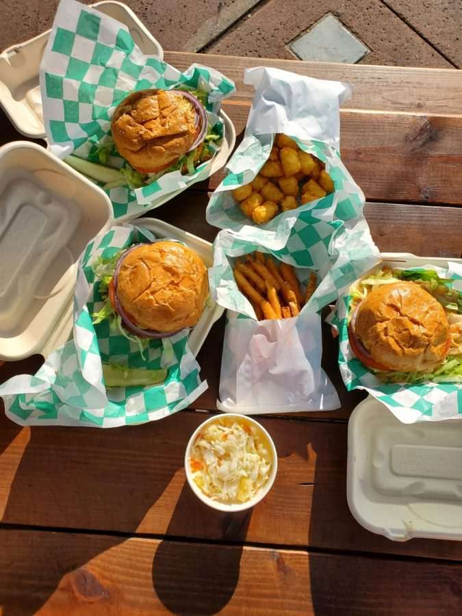 A+picture+of+plant-based+burgers+wrapped+in+green+and+white+paper%3B+pictured+with+a+side+of+french+fries%2C+tater+tots+and+pineapple+coleslaw.