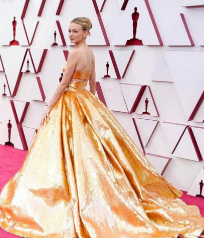 Actress Carey Mulligan in a top-fitted gold Valentino gown with a full skirt on the red carpet.