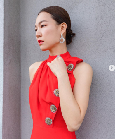 """The """"Minari"""" star Han Ye-ri poses in a red Louis Vuitton dress with golden suns down her left side to her waist."""