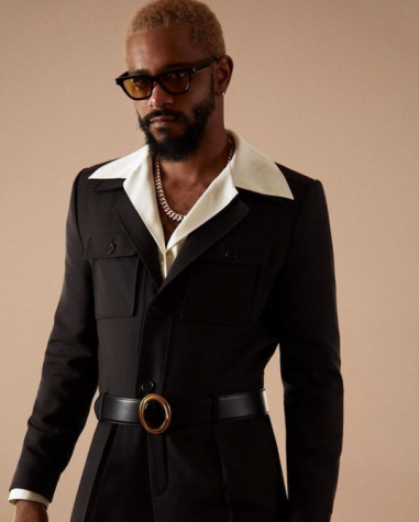 LaKeith Stanfield in a black 70's inspired suit with a white undershirt, collar unbuttoned and flattened.