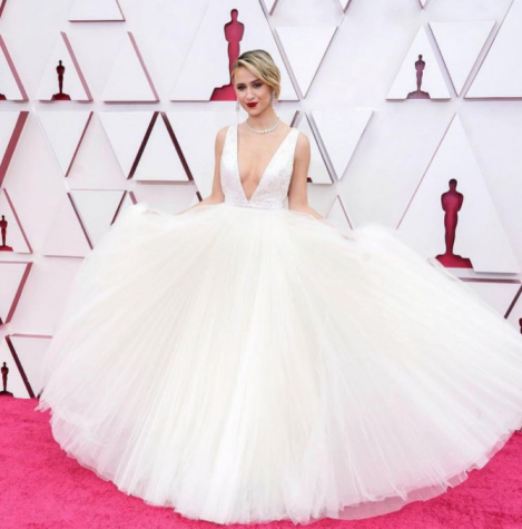 Maria Bakalova holds out her pure white tulle dress. The top is sleeveless with a plunging neckline.