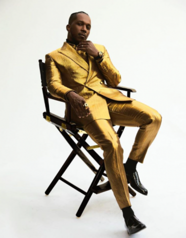 Leslie Odom Jr. sits on a dark director's chair wearing a gold Brioni suit.