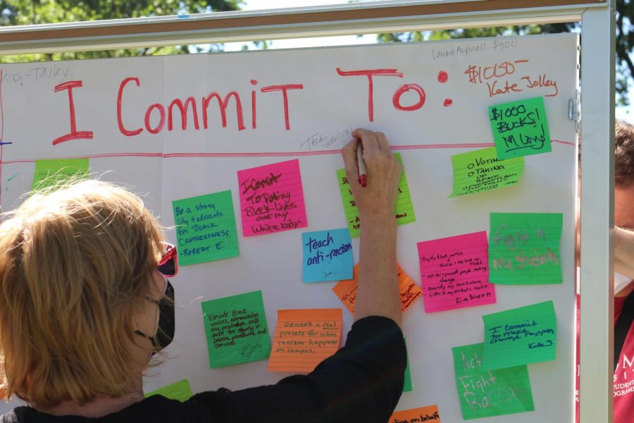 Participant writes a pledge amount to fund a Black student success center among other participants' commitments to end systemic racism at SRJC.