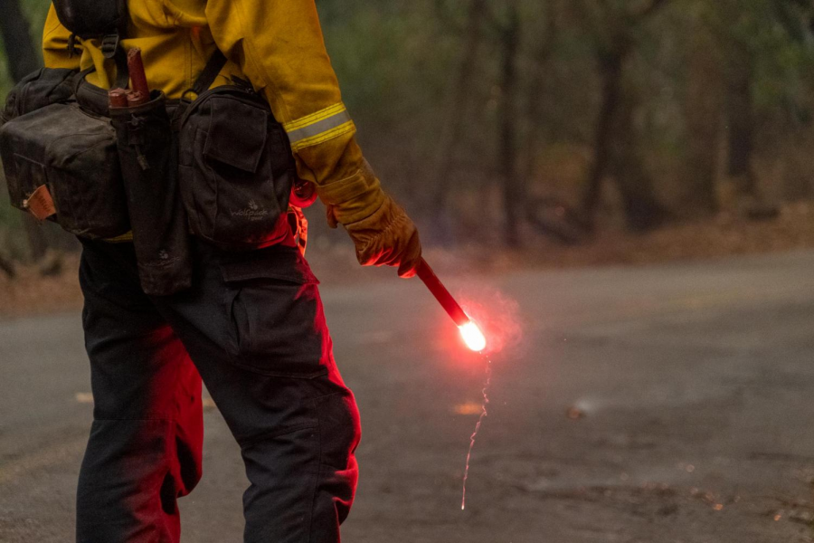 A fireman seen from the elbow down holding a lit flare.