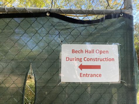 A laminated sign posted on a construction fence points students to the entrance of a building.