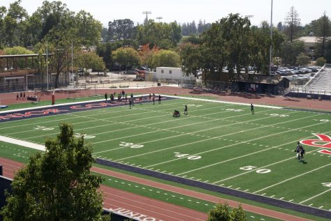 An overhead view shows football players practicing on a new football field.