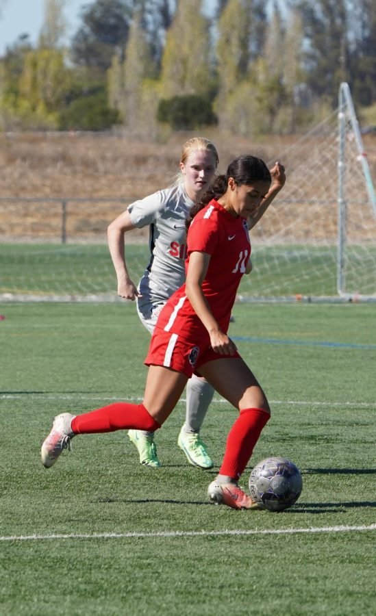 Midfielder Katherine Monroy rushes past a Sierra defender to pass to her teammate during the first half of the game.