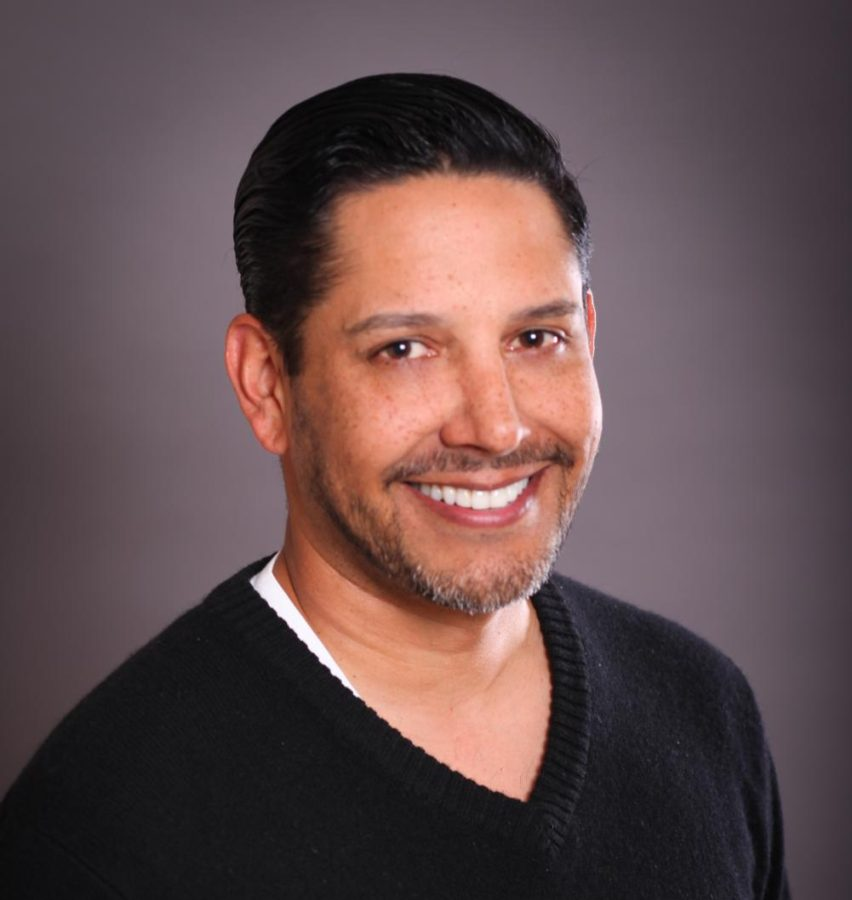 Dr. Michael Valdovinos sits for a professional portrait in a black V-neck sweater